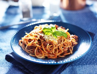delicious spaghetti in bolognese sauce with basil garnish