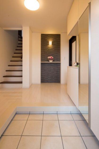 玄関ホールもホワイト×ブラック を基調色とした洗練空間。1階フ ロア全体がフルフラット仕様のた め、お母さまも安心して移動できる。 また、廊下の壁には、将来、手すり も設置可能な下地を採用